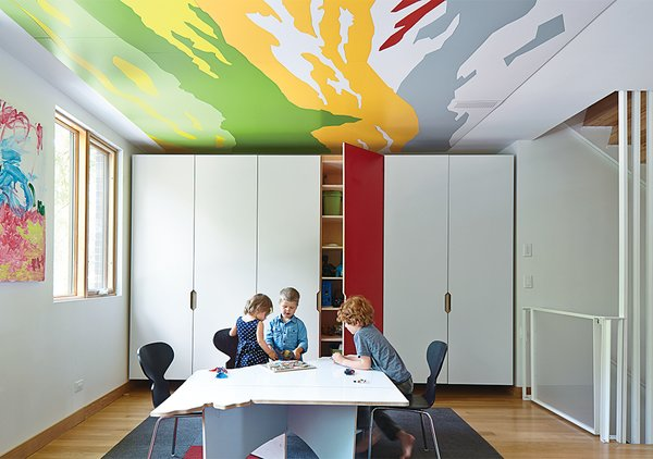 This children's room and playroom caters to one family's young kids with built-in cabinetry that allows the mess to be hidden away. Hufft designed this marker-board table, which was cut in the shape of Missouri. The ceiling features abstract details from Thomas Hart Benton paintings.