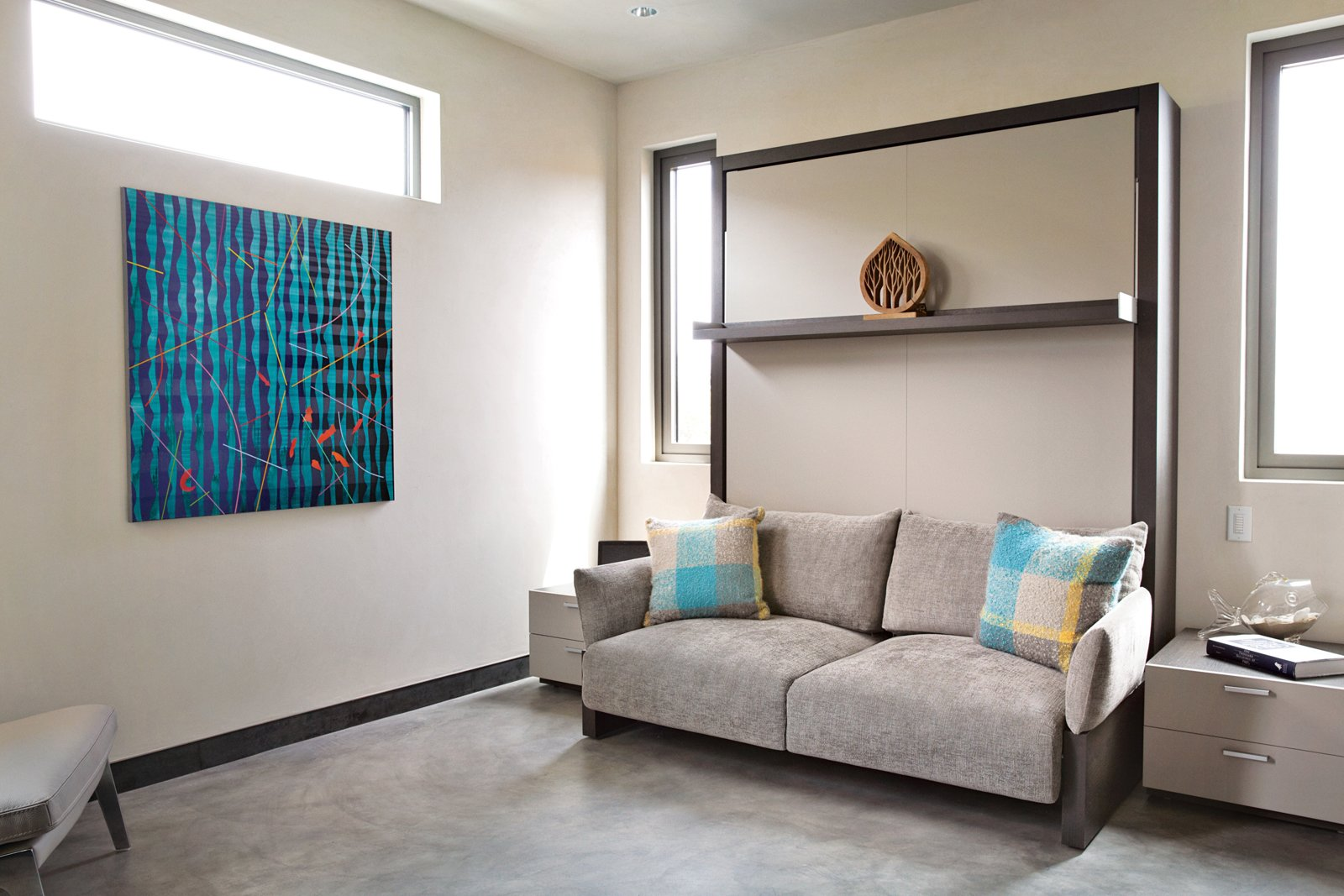 In a bedroom that's used for guests, Robin demonstrates a foldable Murphy bed system, the Nuovoliola '10 from Clei/Resource Furniture. The artwork, Orange Fish, is by Pablo Campos.  Photo 6 of 18 in Actor Bryan Cranston's Green Beach House Renovation