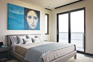 In the master bedroom, Azul Giorgione by Alberto Gálvez hangs above a locally manufactured bed from Soluzioni. The sheets, pillow cases and blanket are from Restoration Hardware; the decorative pillows and quilted coverlet are from Bed, Bath, and Beyond.