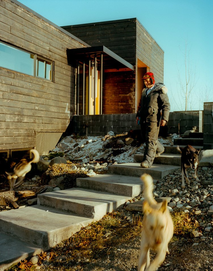 Outdoor and Walkways Perched on top of a hill, the house is accessed by a long staircase that runs up to the exterior courtyard. The dogs, naturally, take their own route.  Photo 17 of 20 in This Modern Cabin Is the Ideal HQ For a Family in Alaska