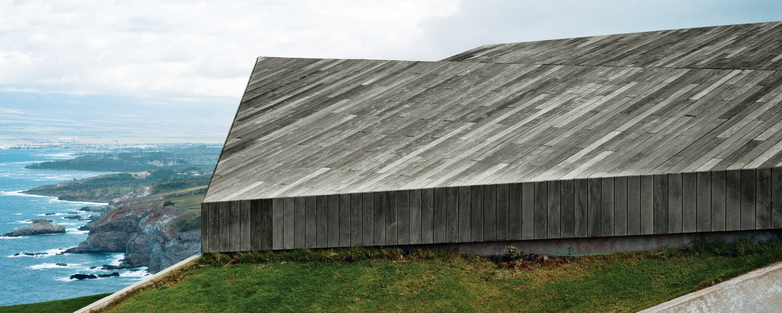 """Exterior, House Building Type, and Wood Siding Material """"In this house, the roof is the only facade—the rest is dissolved beneath it."""" —Architect Aljoša Dekleva  Photo 3 of 11 in Secrets You Need to Know When Using Wood in Wet Spaces from Clifftop House with Angled Roof in Maui"""