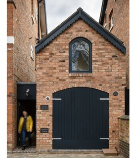 Faux timber doors, painted black, along with a brick facade help the dwelling blend with its surroundings: the Victorian homes of the Moseley neighborhood in Birmingham, UK.