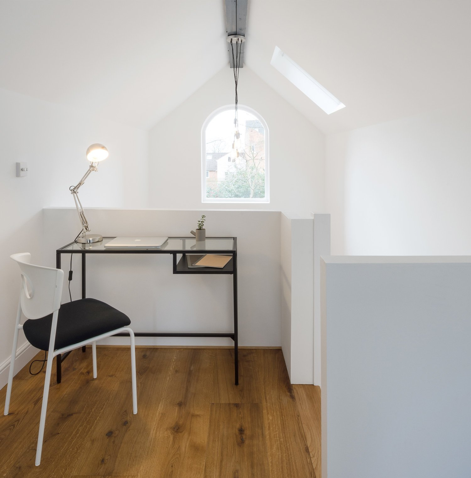 A compact workspace is perched atop the mezzanine level and has views to the garden in the rear.  We Love This Adorable Writer's Studio Camouflaged as a Coach House by Zachary Edelson