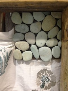 Natural pebbles join fabric on Broeder's board.