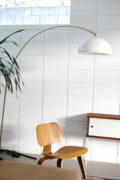 The living room is populated with a molded plywood Eames chair and a vintage Italian lamp.