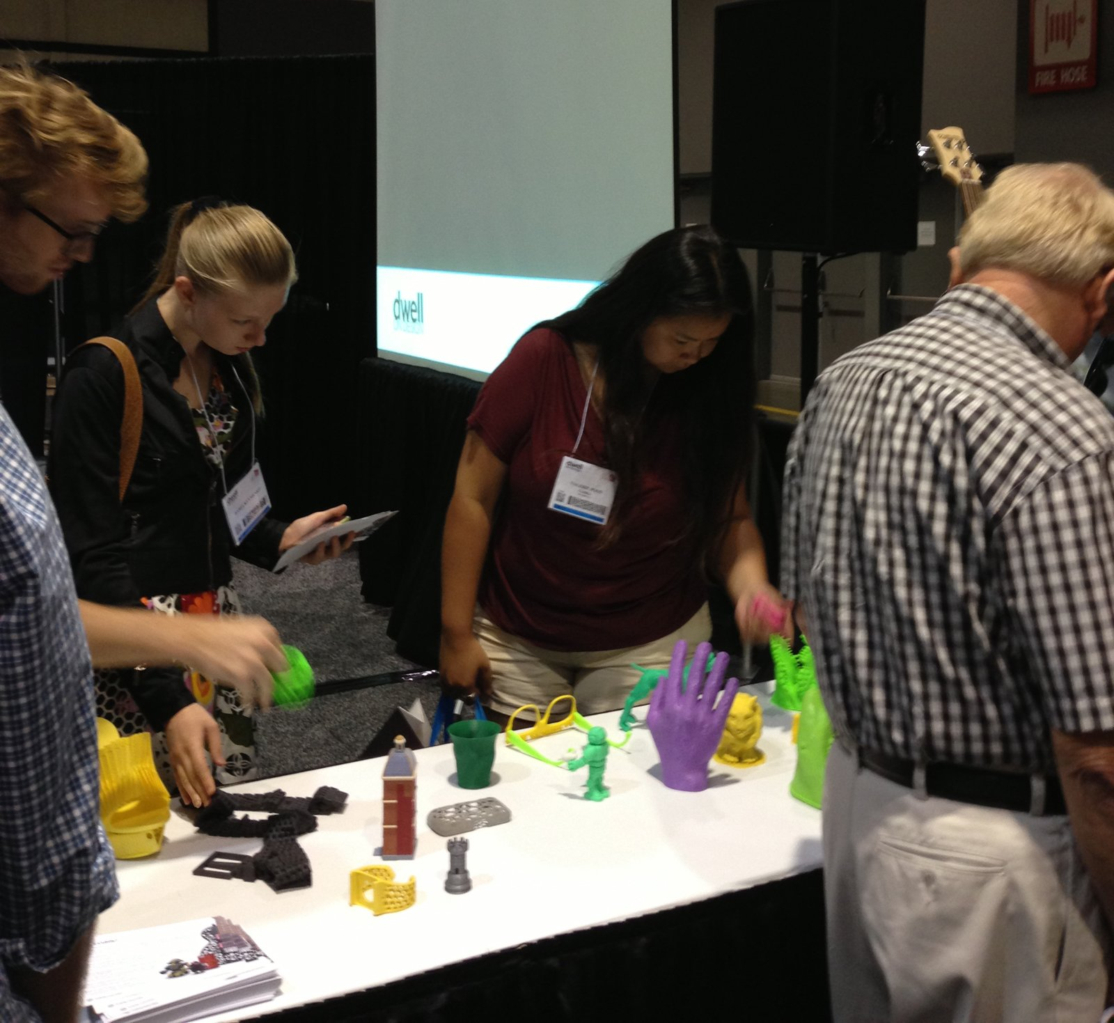 Dwell on Design visitors inspect objects printed on the Cube, a 3D printer.  Photo 2 of 3 in Recap: 3D Printing Demo by Cubify