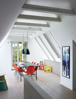 Charrier transformed a cramped attic into a sunny dining room with Vitral windows and white-tinted pine floors by Dinesen. The Sara table is by Hay, the Shell chairs are by Charles and Ray Eames, and the artwork is a hand-printed textile she had framed.