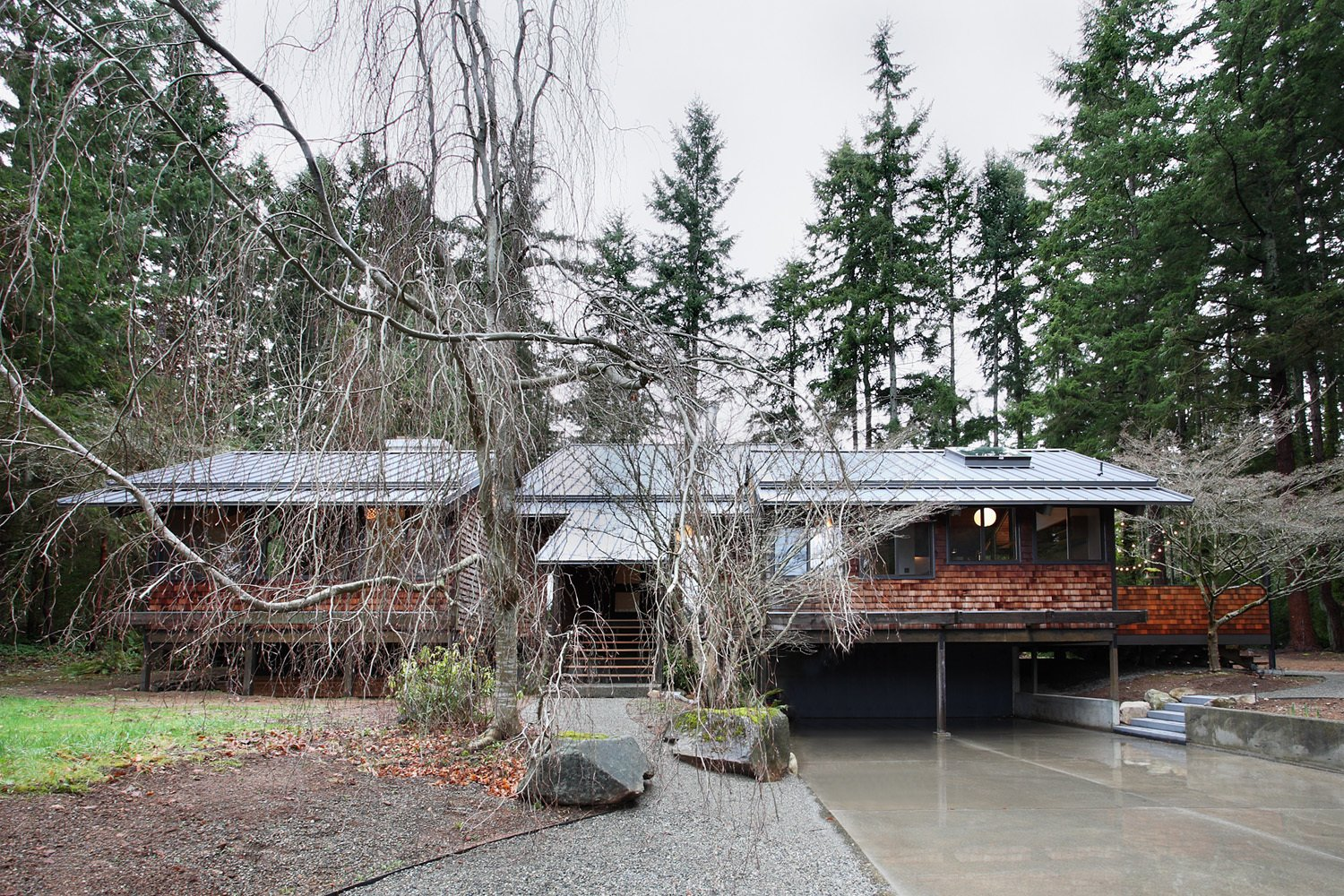 Nestled in a grove of Douglas fir trees, the house stands on series of wooden pylons in a Japanese-inspired fashion. Residents ascend the stairs, center, to reach its single floor. The exterior wooden shingles were intact and are original to the design.  Zema Redux by Zachary Edelson