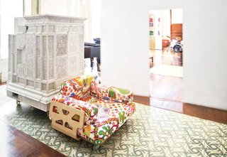 Layer by layer, a crumbling 18th-century flat in the middle of Barcelona finds new life at the hands of architect Benedetta Tagliabue. Paths of Andalusian tile and intervening plaster walls help to delineate space in the expansive apartment, which is centered around an internal entry courtyard. The armchair, designed by Peter and Alison Smithson, is covered in a Josef Frank textile from Just Scandinavian. The white piece just behind it is a repurposed Austrian stove that's now used as a storage device.
