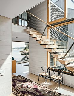 To create continuity between inside and out without overpowering guests and residents, the interiors of this home in Connecticut are clad in bleached white cedar boards, while the exterior is sheathed in more traditionally unfinished cedar boards that can age over time. The lighter finish on the interior feels beachy and relaxed, and acts as a neutral foil for traditional and modern furnishings.