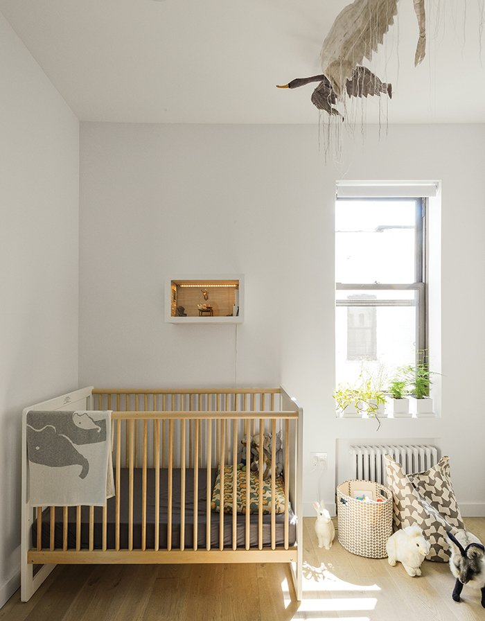 Schmidt selected Oeuf's Robin crib for Finn's soon-to-be sibling. The bird mobile is by Tamar Mogendorff. Tagged: Kids Room, Playroom, and Bedroom.  Photo 6 of 14 in How One Family of Three Does It All in 675 Square Feet