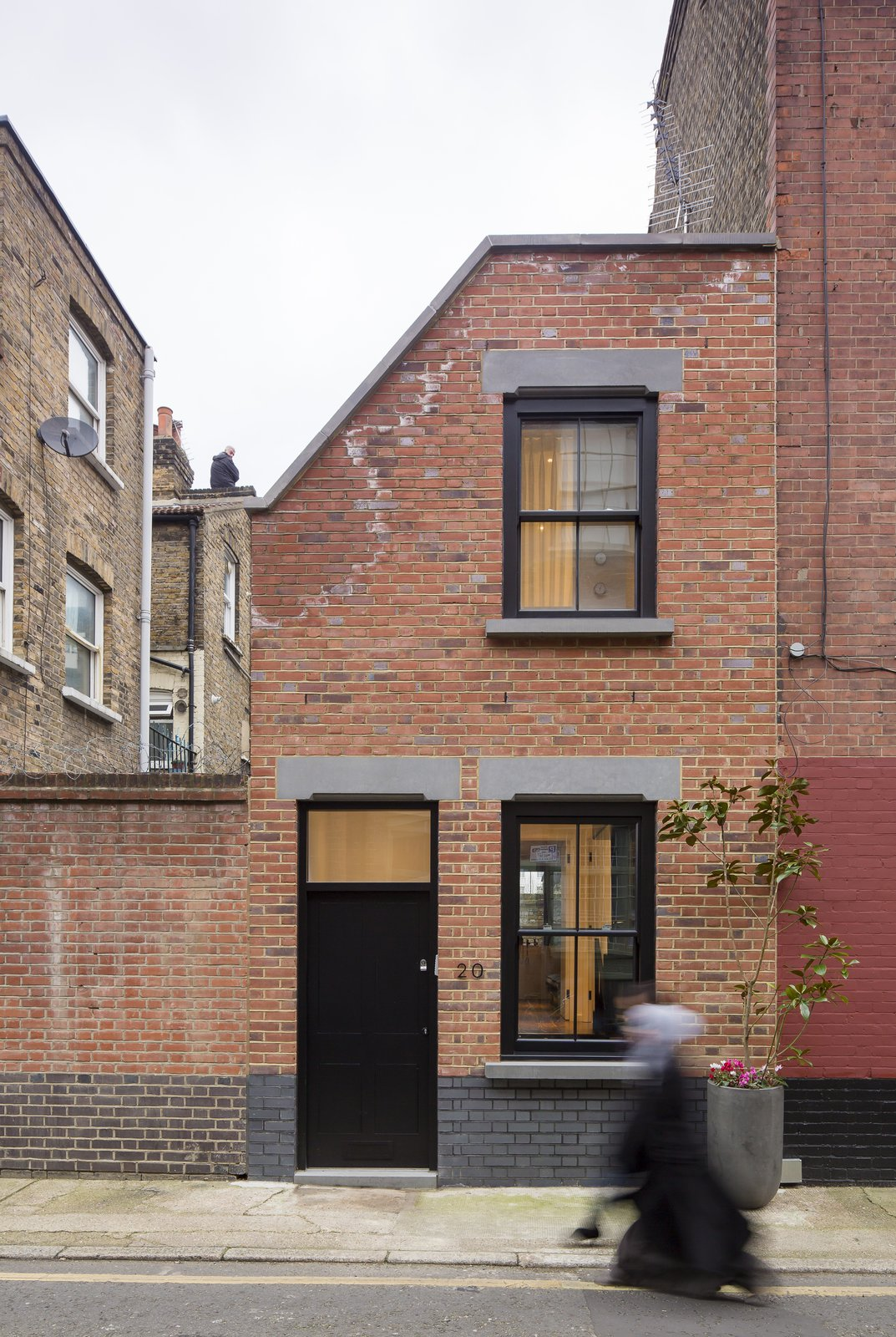 Set in a conservation area, the home's façade was designed to blend into the street's terrace style. To that end, it is clad in red bricks from Traditional Brick & Stone and punctuated with sash windows. The concrete toned lintels hint subtly at the modernity that lies within.  Photo 10 of 21 in A Spotlight on 10 Traditional Homes with Modern Interiors from Cleverly Stacked Floors Form a Roomy House On a Tight Lot