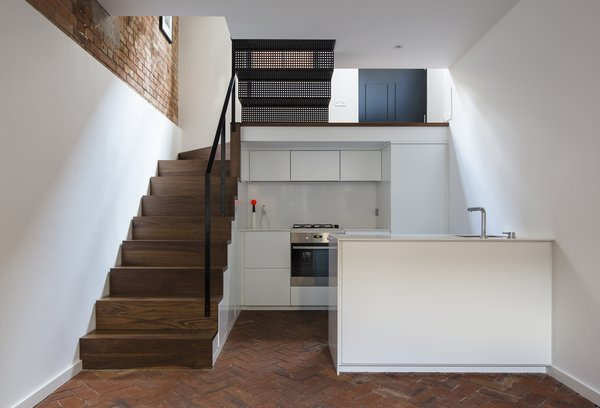 The kitchen is situated in a sunken basement, underneath the staircase's walnuts steps. The same joiner who built the house's timber elements built the white cabinetry which are finished in a 40% gloss lacquer. Silestone countertops and integrated appliances maintain the space's simple lines. Additional storage is fitted under the staircase.