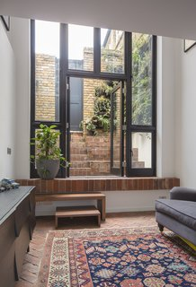 The home's living room is located on the lower level, opposite the kitchen. The herringbone-patterned brick floor is partially covered by a carpet purchased in Istanbul. A sofa and Muuto sideboard anchor opposite sides of the space.