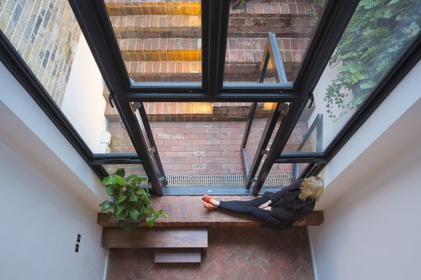 Viewed from above, the lower level's brick floors establish a sense of continuity between the living spaces and the outer courtyard. Two-stories of glazing ensure that the lower levels never feel gloomy.  Cleverly Stacked Floors Form a Roomy House On a Tight Lot by David Rudin