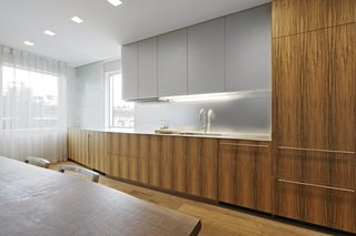 """A wall of custom cabinets made with Paldao wood veneer defines the kitchen. """"We wanted them to be as clean and minimal as possible but to have a warm texture,"""" Slade says. """"The aluminum countertop, resin upper cabinets, and satin mirror glass backsplash are designed to reflect light."""""""