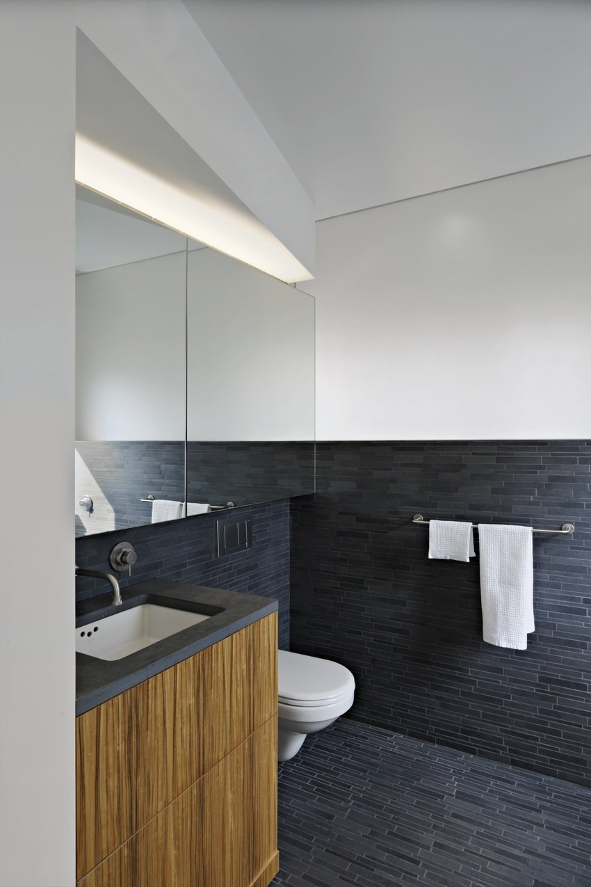 "Bath Room, Ceramic Tile Floor, One Piece Toilet, Undermount Sink, and Ceramic Tile Wall The master bath is clad in Area tiles from Mirage.  Search ""how design gray"" from Modern Dream Penthouse in New York City Makes the Most of Natural Light"