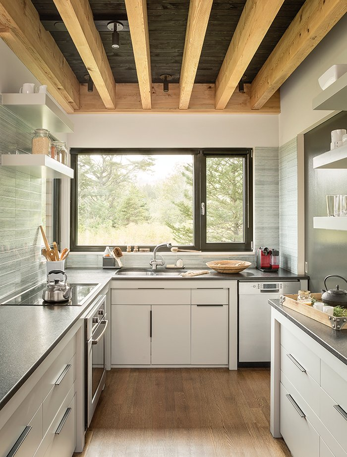 "Kitchen, Medium Hardwood Floor, Granite Counter, and Porcelain Tile Backsplashe Cambrian black granite countertops were installed in the kitchen. ""One of the favorite things I have to do in the kitchen is wash dishes, just because it's such a delightful view out the window,"" Bullitt says.  Photo 3 of 7 in An Artist Builds a Wooden Home That Lets Nature Be the Boss"