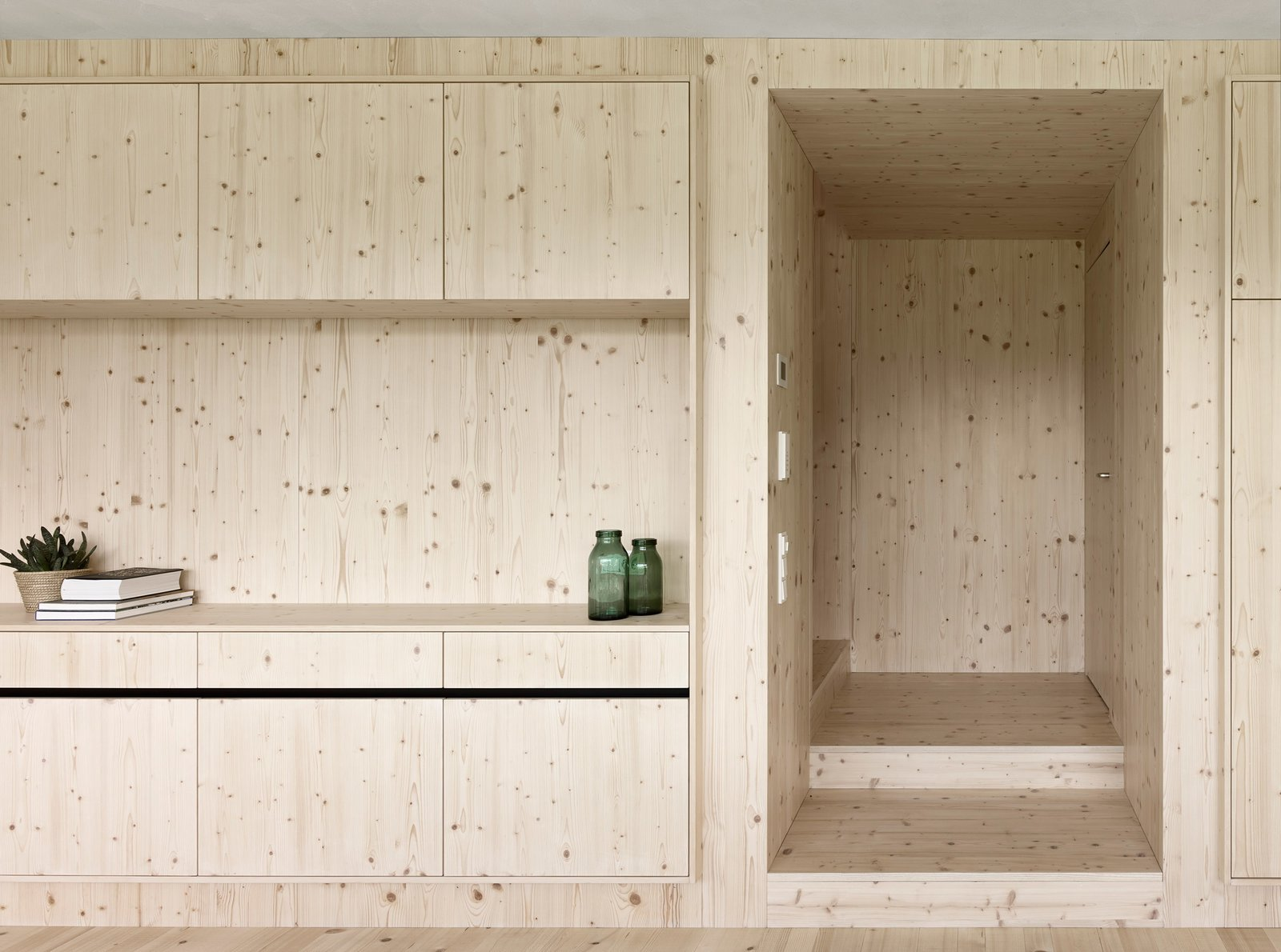"""Built-in shelving crafted by local carpenters distinguish the living area from the service zone, where appliances and utilities are stored. """"Because of the integrated shelving, no additional furniture is needed for storage,"""" Matt says.  Composition from House For Julia Björn"""