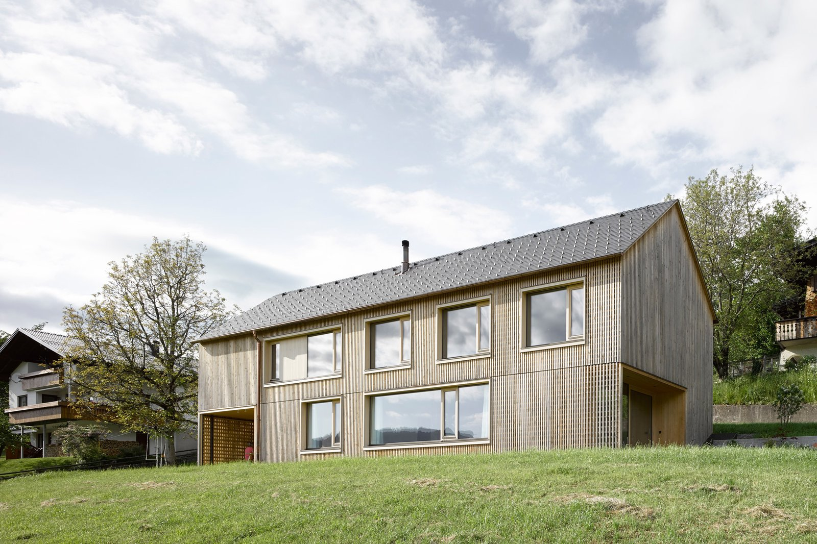 The house's simple gable form helps the house blend in with its neighbors.  Photo 10 of 10 in A Simple Gabled House Features an Intricate Latticework Shell