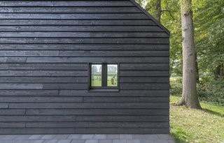 "In keeping with Scandinavian building traditions, locally sourced Douglas fir clads the exterior. ""The clients like the simplicity of [local] barns,"" Koolhaas says. The black paint also helps draw in heat, which is important in the region's cold climate."