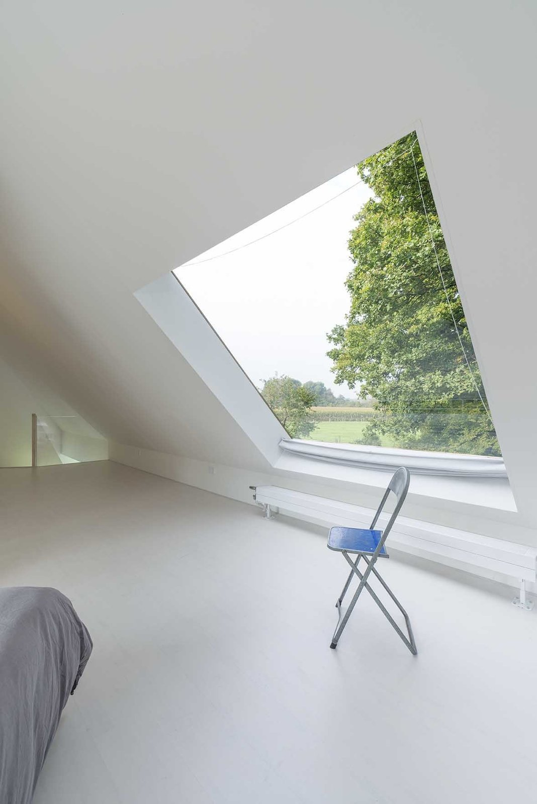 In the upstairs bedroom, a square skylight opens to a patch of sky.  Triangular House by Laura C. Mallonee