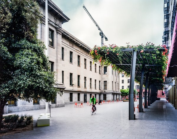 Once a derelict urban alley, Mint Plaza is nestled between the Old Mint and several historic warehouses. A simple ground plane unifies the plaza, while a steel arbor balances the towering warehouses to the north and the lower neoclassical facade of the Mint building to the south. The climbing vines on the arbor bring extensive greenery to the heart of the plaza and provide a canopy for al fresco diners. Photo by: Jeremy Blakeslee.  Contemporary Architect: CMG Landscape Architecture (2008)