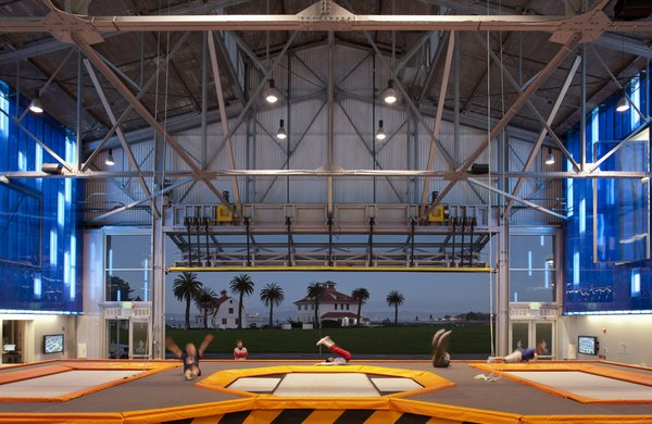 The U.S. Army's former airplane hangars on Crissy Field posed a complex rehabilitation challenge for the Presidio Trust. Fortunately, the House of Air, a trampoline gymnasium, offered a new use that capitalized on this hangar's large, open interior, steel trusses and slightly gritty character. New components were skillfully placed within the cavernous structure, with the architect riffing on its aviation history to produce a bright, playful interior where people can literally take flight. Photo by: Ethan Kaplan.  Original builder: U.S. Army (1921)   Contemporary architect: Mark Horton Architects (2011)