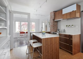 """A door frame was preserved as """"a sculptural memory piece,"""" Sara Imhoff says, after a wall separating the old kitchen from a small dining room was demolished. The countertops and backsplash are by Caesarstone."""
