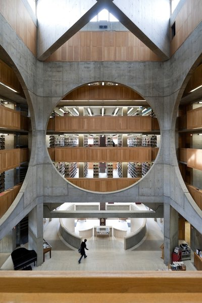 """Library at Phillips Exeter Academy (Exeter, New Hampshire: 1972)  Kahn opened up the interior of this brick library with a ceiling clerestory, which allowed sunlight to flow in and colorfully contrast with the stone-and-wood interior. Illumination was a focus down to the smallest detail, such as the teak study corrals positioned in light-filled spots. It's a fitting response to the design committee's brief, which noted that """"the quality of a library, by inspiring a superior faculty and attracting superior students, determines the effectiveness of a school."""""""