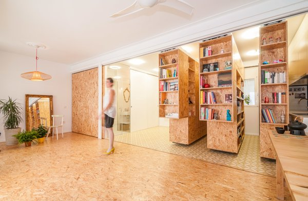 Three deceptively simple shelves made of particleboard are the house's main structural elements. By pushing any one of the units, the resident can easily reposition it; they slide left or right with a simple track system.