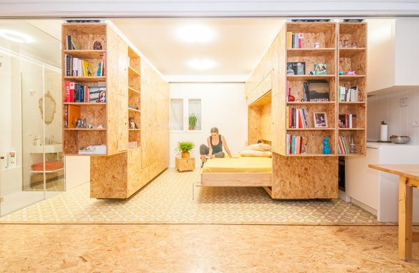 Madrid-based firm PKMN dreamed up this flexible concept for a client with a tiny home north of the city. Made up of three shelving units on track system, the All I Own House can be configured in countless ways, making space for a bedroom, kitchen, sitting area, changing room, and more. Shown here is a horizontal Murphy bed, which makes a great space-saving solution as well as  a comfortable sleeping space.