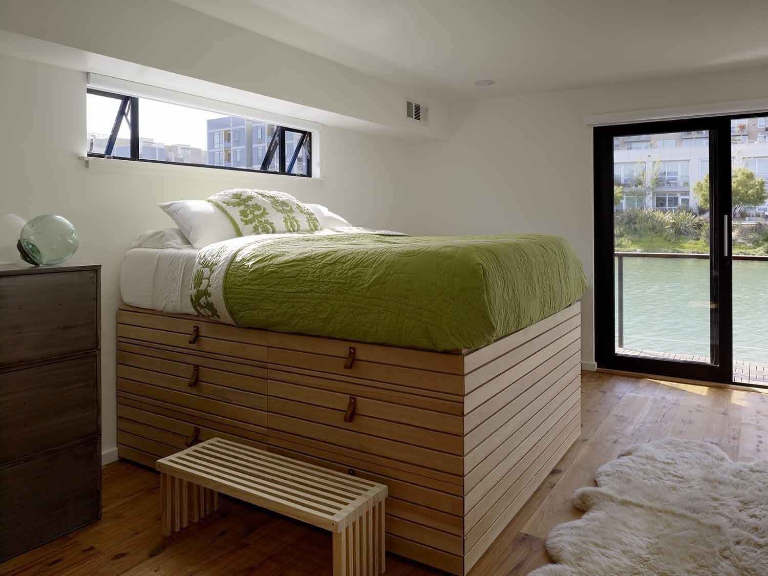 Bedroom and Bed In the second floor master bedroom, a custom captain's bed designed by the homeowner, features drawers and storage underneath. Its towering height allows for views out the nearby window.  Bedrooms by Dwell from Like a Loft on Water