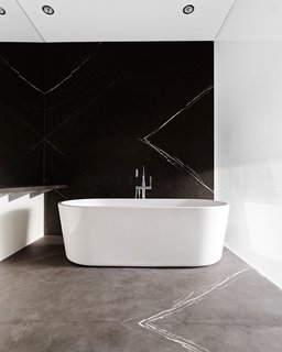 In a home largely outfitted in wood, this marbled bathroom designed by Peter Russell-Clarke and Craig Steely provides a respite for the eyes, with its white, gray, and black palette and minimalist fixtures and details. Dramatic veining in the stone provides visual interest and movement, and the freestanding bathtub contrasts with the dark marble on the wall behind.