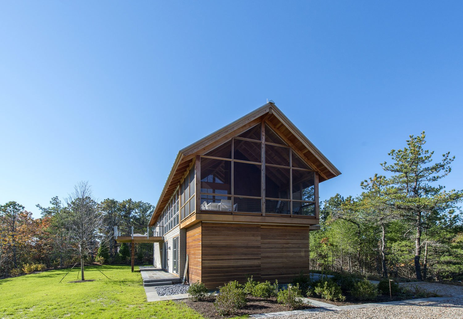 """""""The typical Cape Cod house built by early settlers had very few windows, as they were built to survive a harsh winter,"""" Hammer explains. The architect emulated their recognizable form with a 9/12 pitched gable roof but added plenty of contemporary glazing for natural light and ventilation.  Modern Homes with Cedar Facades by Andrea Smith from A Modern Take on the Gabled Cabin in Cape Cod"""
