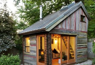 A polychrome facade made of salvaged, 100-year-old barnwood gives this small, lofted cottage space its unique character. Its copper roof is also reclaimed, a lucky Craigslist find from a local remodel. Though the structure has a footprint of just 11' x 14', it provides a useful space to entertain, catch up on work, or relax.