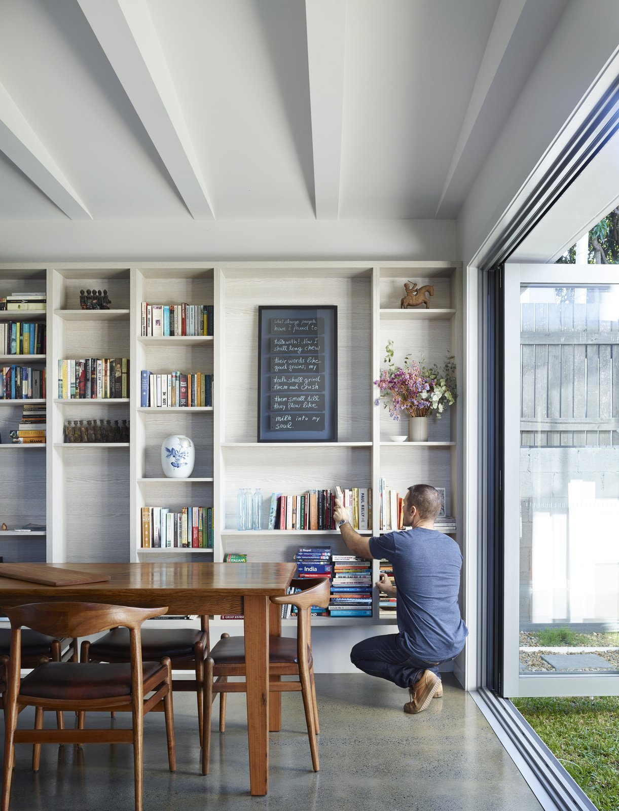 """""""Working with the narrow qualities of the site, the internal spaces of the kitchen and main living areas can open completely to double them in size,"""" O'Neill said. The architecture firm built a custom bookshelf using drifted oak with the warm Ravine finish by Polytec.  Annie Street by Kelly Dawson"""