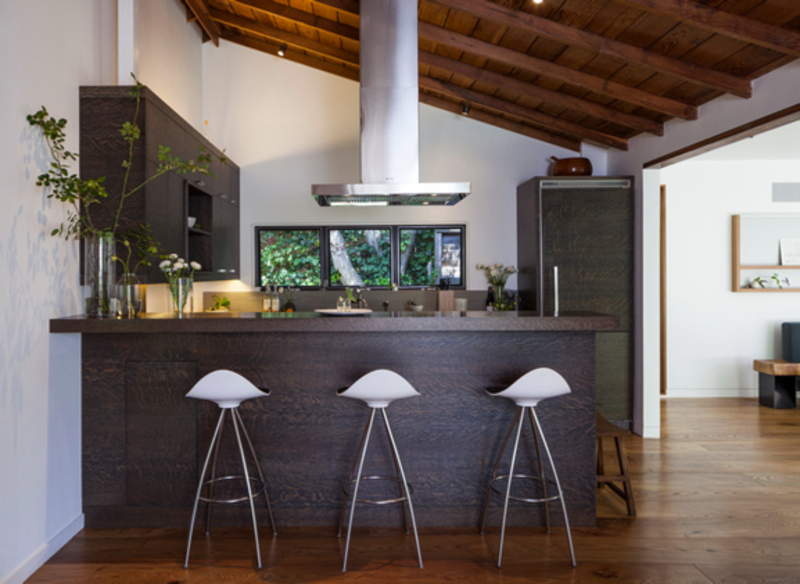 A new kitchen in the old part of the building contrasts sleek dark wood millwork with the original vaulted ceilings, which Gargan and Wagner scrubbed and sanded themselves to reveal the old-growth redwood.  Kitchen from Inside a Renovated Cottage in Marin