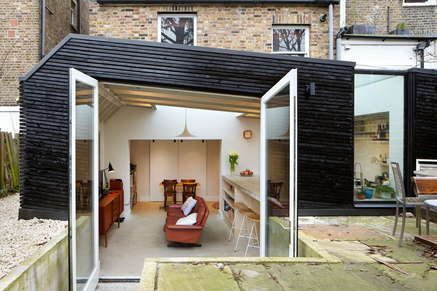 The slightly below-ground kitchen sits inside a boxy extension, clad in recycled timber and stained kettle black. A wildflower garden grows on its pitched roof. Tagged: Doors, Exterior, and Swing Door Type.  A Modern Addition Gives a London Chef a Dream Kitchen by Laura C. Mallonee from Unexpected Additions in London