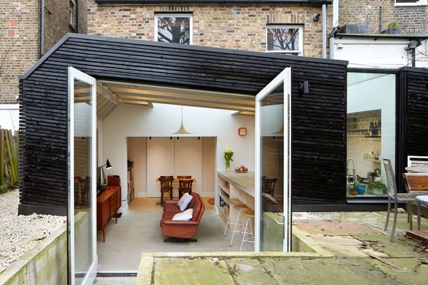 The slightly below-ground kitchen sits inside a boxy extension, clad in recycled timber and stained kettle black. A wildflower garden grows on its pitched roof.