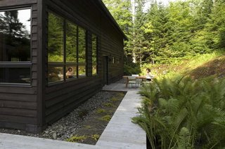 Economical, plentiful, and homely, wood was a natural fit for the project. In back, a modest deck area offers an escape from cabin fever during the warmer months.
