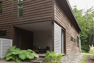 A large porch is a common characteristic of Quebec architecture. In keeping with the residents' desire to live more sustainably, the firm sourced salvaged wood for the exterior slats.