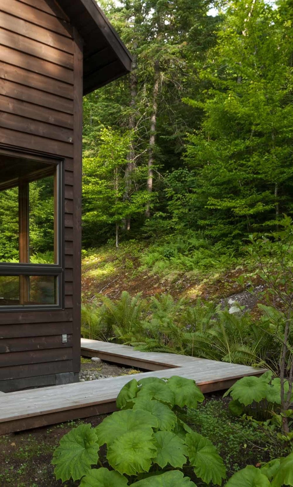 Large windows make the forest a constant presence indoors.  A wood walkway runs along the perimeter of the house.  Cabin from A Nordic-Inspired Woodland Cabin in Quebec