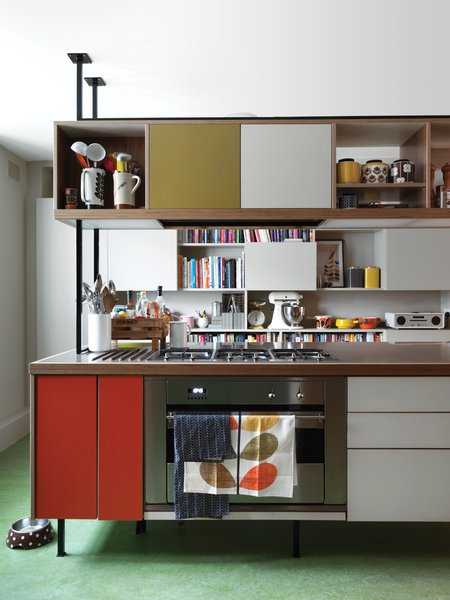 """Kitchen Confidential   Kiely and architect Maxim Laroussi designed the kitchen unit. """"I originally didn't want an island, but I liked what we did because it feels like a piece of furniture. It's cozy to cook around,"""" Kiely says. Panels of orange and olive Formica accent the 1950s-inspired piece, which houses a cooktop by Smeg. A checkerboard of closed cabinets and open shelves offers storage against the far wall for Kiely's collection of dishes, knickknacks, cookbooks, and small appliances, like the KitchenAid stand mixer and radio by Vita Audio. The floor is green Marmoleum, selected because it feels warm underfoot. Kiely's own Stem dish towels and ceramic storage jars add more lively color to the room."""