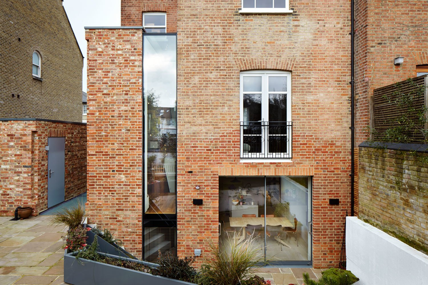 A tall and narrow window separates the new brickwork from the historic building, making its lines and profile clearly understandable.  Raconteur Renovations: Homes with Some Serious History by Matthew Keeshin from Lantern Home
