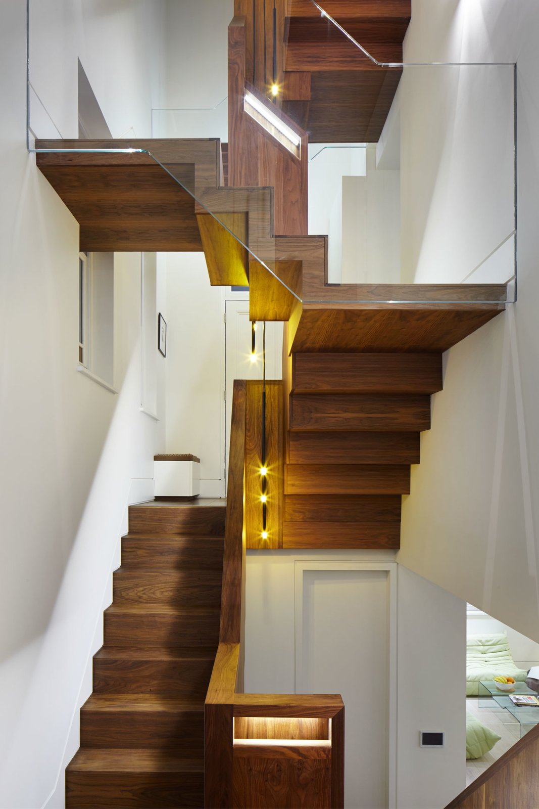 """The architects replaced the original, carpeted stairway with one built from black walnut. """"[The goal] was to mirror a large tree that had to be felled in the garden before the project started,"""" Webster explains. """"The staircase rises up through the building, with the branches being the landings that reach out to the different rooms."""" Tom Dixon lights hang at the center of the stairs.  190+ Best Modern Staircase Ideas from Lantern Home"""