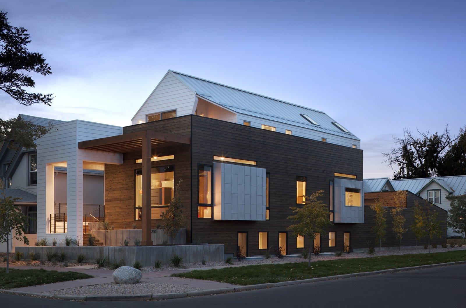 "Exterior, Wood Siding Material, Metal Siding Material, House Building Type, and Metal Roof Material Apart from a ""generous"" master bedroom, Mitchell says that the couple also wanted a rooftop deck to see views of downtown Denver. A sloped roof kept the building up to code, and the outdoor deck ""was achieved by shifting the upper volume backwards from the front of the house,"" he says.  Photo 8 of 8 in A Couple's Denver Residence Makes Clever Use of a Narrow Plot from Mile High Design: 5 Modern Homes in Denver"