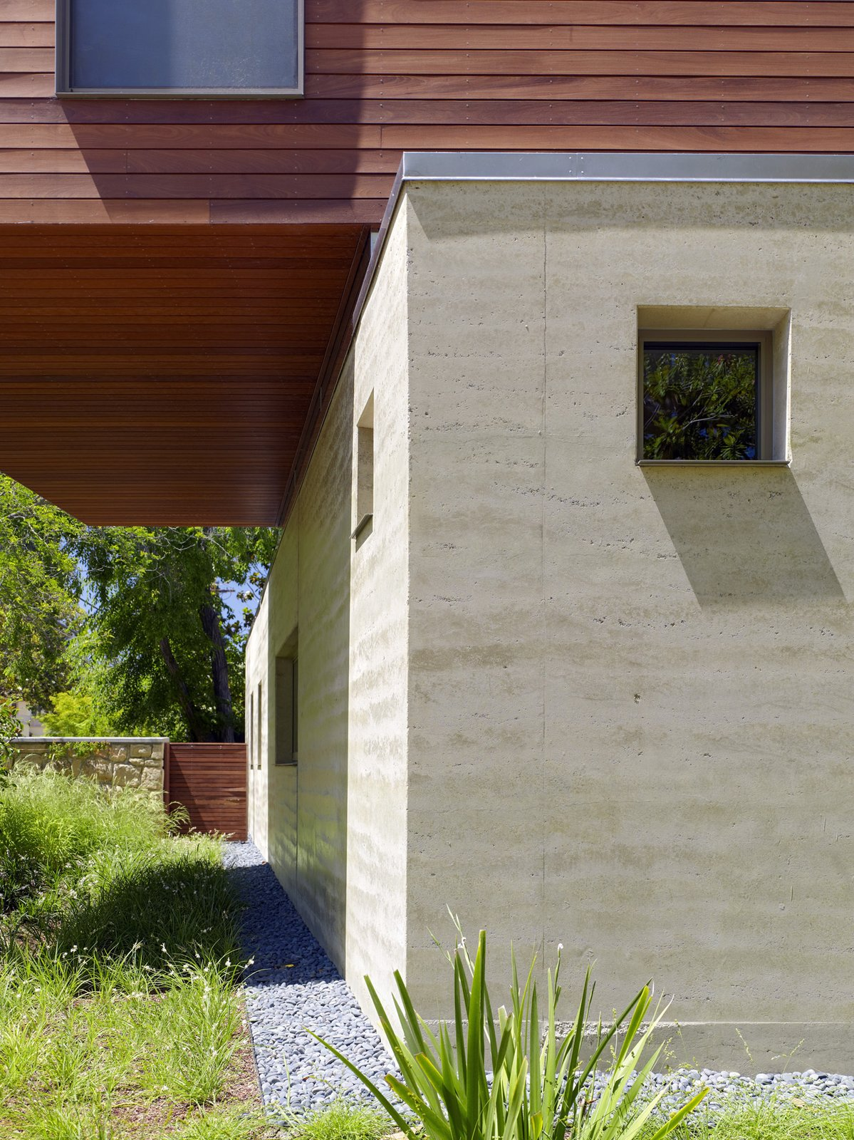"""Exterior, Wood Siding Material, Flat RoofLine, and House Building Type """"We originally proposed using concrete for the walls because we like the plain style and directness,"""" the owners say. Instead of concrete, Smith suggested rammed earth, a material that combines some of the physical properties of concrete, but is less """"psychologically cold."""" The 16-inch-thick walls' thermal mass helps to insulate the interior from heat in the summer and cold in the winter.  """"Rammed earth is complicated,"""" says Smith, """"so have the right expectations, do the research, and hire the right people."""" David Easton—who Smith calls """"The Godfather of Rammed Earth""""—headed the contracting team that built the walls.  Great Earth Homes by Kelsey Keith"""