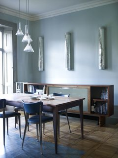 """The center of the dining room is marked out by a """"carpet"""" of terracotta, turquoise and green cement tiles from Emery & Cie. They are a practical, hard-wearing floor surface for a high-traffic area."""