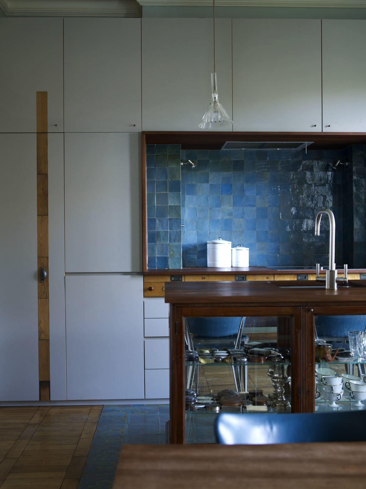 The gray units in the kitchen benefit from the addition of salvaged drawer fronts running in vertical and horizontal strips.  Photo 3 of 12 in A Gracious London Terrace House Is Reborn with Salvaged Materials